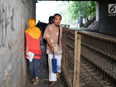 Pejalan kaki melintasi jalan setapak di sekitar Stasiun Cawang, Jakarta, Kamis (9/5). Meskipun sempit, jalan setapak tersebut masih menjadi pilihan sebagian pejalan kaki untuk menyeberangi Jalan Gatot Soebroto, dibanding harus melewati JPO yang jaraknya lebih jauh. (Liputan6.com/Immanuel Antonius)