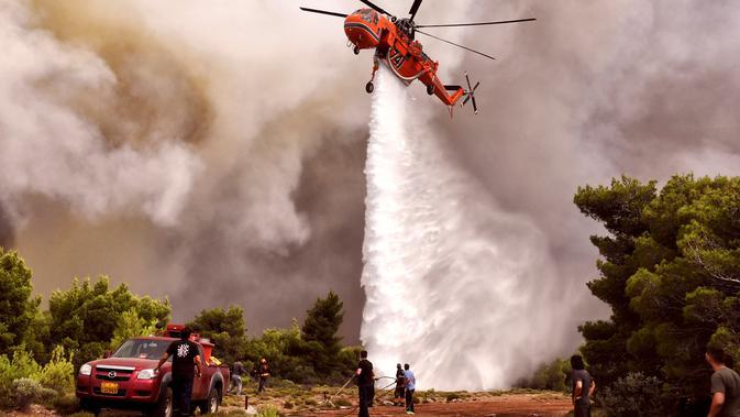 Helikopter pemadam kebakaran menjatuhkan air untuk memadamkan api saat kebakaran di Desa Kineta, dekat Athena, Rabu (24/7). Selain menewaskan puluhan orang, api juga melahap rumah, mobil, dan hutan. (AFP Photo/Valerie Gache)