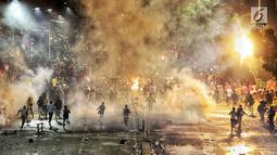 Massa berlari saat Polisi menembakan petasan dan gas air mata ke kerumunan massa di kawasan Pejompongan, Jakarta, Senin (30/9/2019). Demonstrasi menolak UU KPK hasil revisi dan RUU KUHP di depan Gedung DPR/MPR berakhir ricuh. (Liputan6.com/JohanTallo)