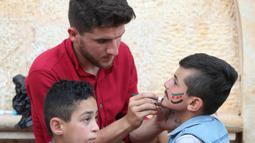 Seorang pria Suriah melukiskan bendera oposisi Suriah di wajah seorang anak selama perayaan Idul Fitri, hari libur Muslim yang dimulai pada akhir bulan puasa Ramadan, di Binnish di provinsi Idlib yang dikuasai pemberontak di barat laut Idlib (26/5/2020). (AFP Photo/Omar Haj Kadour)