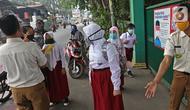 Sejumlah murid  memasuki sekolah  SD Negeri 6, Bekasi, Jawa Barat, Selasa (4/8/2020). Pemerintah setempat memberikan izin kepada enam sekolah untuk melakukan uji coba pembelajaran tatap muka selama satu bulan. (Liputan6.com/Herman Zakharia)