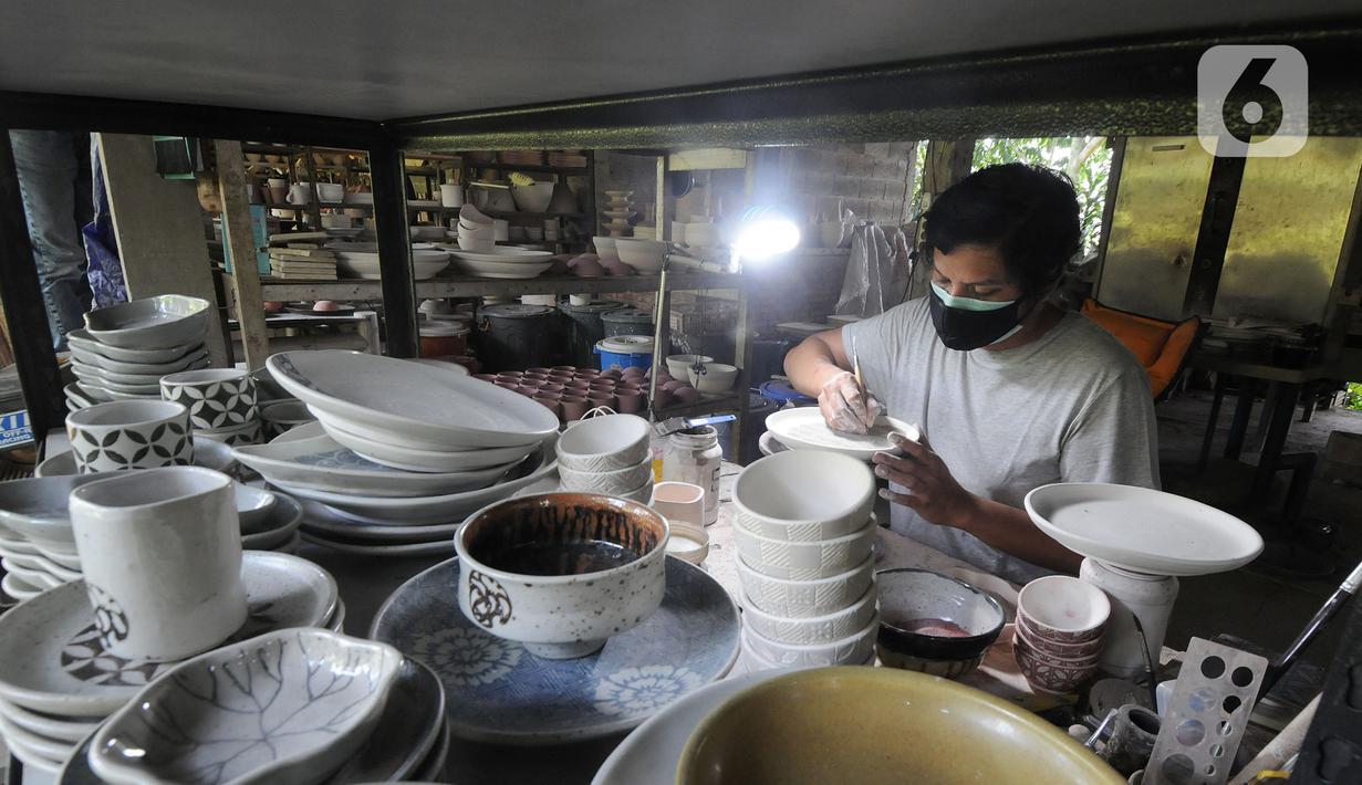 Perajin menyelesaikan pembuatan keramik secara handmade di Pekunden Pottery, Bojongsari, Depok, Jawa Barat, Rabu  (22/9/2021). Produksi keramik rumahan tersebut mampu bertahan di masa pandemi dengan mengandalkan jaringan offline dari mulut ke mulut. (merdeka.com/Arie Basuki)