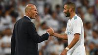 Pelatih Real Madrid, Zinedine Zidane (kiri) bersalaman dengan Karim Benzema merayakan kemenagan atas Barcelona pada Piala Super Spanyol 2017 usai pertandingan melawan Barcelona di stadion Santiago Bernabeu, Spanyol (16/8). (AFP Photo/Gabriel Bouys)