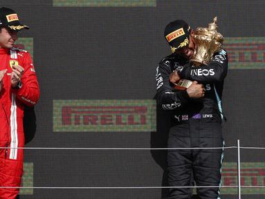 Pembalap Mercedes, Lewis Hamilton (kanan) berhasil meraih podium juara F1 GP Inggris, Minggu (18/7/2021) malam WIB. Sedangkan pembalap Ferrari Charles Leclerc menempati posisi kedua dalam balapan tersebut. (Foto: AFP/Adrian Dennis)