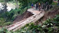 Jembatan darurat yang terbuat dari beberapa batang pohon ini dibuat agar masyarakat dapat menjalankan aktifitas keseharian.