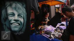 Pengunjung saat melihat kaos Bon Jovi yang dijajakan pedagang di luar Stadion Gelora Bung Karno, Jakarta, Jumat (11/9/2015). Grup band asal Amerika itu akan menggelar konser 'Bon Jovi Live! Jakarta' nanti malam di arena GBK. (Liputan6.com/Faizal Fanani)