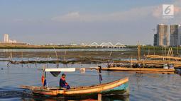 Nelayan melintasi area permukaan air laut yang menyurut di sekitar pesisir Kamal Muara, Jakarta, Kamis (15/3). Fenomena turunnya permukaan air di daerah ini lebih terlihat jelas ketika laut tidak pasang. (Merdeka.com/Iqbal S Nugroho)