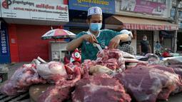 Seorang pedagang menyiapkan daging untuk dijual di sepanjang jalan karena pasar tetap tutup di tengah pembatasan lockdown yang diberlakukan untuk mencoba menghentikan lonjakan kasus virus corona COVID-19 di Phnom Penh, Kamboja, Selasa (11/5/2021). (TANG CHHIN Sothy/AFP)