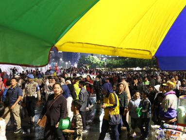 Warga menikmati car free night saat malam pergantian tahun di Jalan MH Thamrin, Jakarta, Senin (31/12). Hujan yang mengguyur Jakarta sejak siang tidak menyurutkan antusias warga menikmaticar free night. (Liputan6.com/Angga Yuniar)