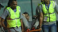 Penjaga gawang Indonesia U-23, Andritany ditandu keluar lapangan saat laga melawan Uzbekistan pada PSSI Anniversary 2018 di Stadion Pakansari, Kab Bogor, Kamis (3/5). Babak pertama imbang 0-0. (Liputan6.com/Helmi Fithriansyah)