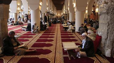 Suasana saat para pria membaca Al-Quran selama bulan Ramadan di Masjid Agung Sanaa, Yaman, Minggu (26/4/2020). Masjid Agung Sanaa merupakan salah satu masjid pertama yang dibangun atas perintah Nabi Muhammad SAW. (Mohammed HUWAIS/AFP)