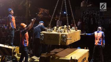 Petugas dibantu alat berat mengevakuasi gerbongKRL Commuter Line dengan nomor KA 1722 jurusan Jatinegara - Bogor di kawasan Kebon Pedes, Bogor, Jabar Minggu (10/3). Proses evakuasi menggunakan crane.(Liputan6.com/Immanuel Antonius)