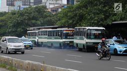 Bus Kopaja menunggu penumpang di Jalan Jenderal Sudirman, Jakarta, Rabu (4/7). Wagub DKI Jakarta Sandiaga Uno melarang angkutan umum seperti Kopaja dan Metromini melintasi jalan protokol selama Asian Games 2018. (Liputan6.com/Arya Manggala)