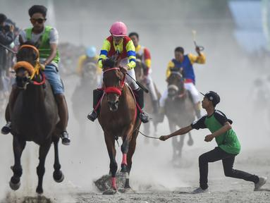 Sejumlah joki muda saling memacu kuda dalam balapan kuda tradisional di Takengon, provinsi Aceh pada 2 Maret 2019. Pacuan kuda tradisional digelar pada hari-hari besar daerah nasional di dataran tinggi Gayo Aceh. (CHAIDEER MAHYUDDIN/AFP)
