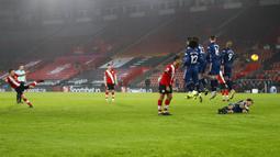 Pemain Arsenal Hector Bellerin berbaring di belakang tembok pertahanan saat rekan satu timnya melompat mengadang tendangan bebas pemain Southampton pada pertandingan Liga Inggris di Stadion St Mary, Southampton, Inggris, Selasa (26/1/2021). Arsenal menang 3-1. (AP Photo/Frank Augstein, Pool)