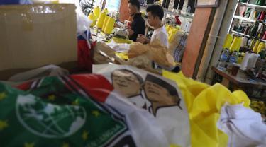 Pekerja menyelesaikan pembuatan atribut partai di Jakarta, Senin (15/10). Dalam sehari, pekerja di pabrik konveksi tersebut bisa memproduksi hingga 2.000 potong atribut partai, mulai dari kaos, bendera, dan topi. (Liputan6.com/Immanuel Antonius)
