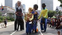 Empat boneka asal Prancis dari Kelompok teater Les Grandes Personnes hibur warga saat CFD di Jakarta, Minggu (9/7). Kegiatan untuk menghimpun dana akan disalurkan ke sejumlah yayasan  di bidang pendidikan anak. (Liputan6.com/Immanuel Antonius)
