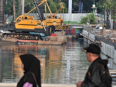 Warga berjalan melintasi turap di Kali Ciliwung Lama, Jakarta, Kamis (11/10). Petugas Dinas Sumber Daya Air Pemprov DKI Jakarta melibatkan alat berat dalam pembangunan turap. (Merdeka.com/Iqbal Nugroho)