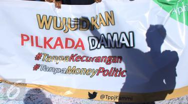 Mahasiswa yang tergabung dalam Tim Pengawal Pilkada Jakarta (TPPJ ) KAMMI menggelar aksi damai pada kegiatan Car Free Day di Jakarta, Minggu (9/4). Mereka menyerukan agar masyarakat menolak money politik dalam Pilkada DKI 2017. (Liputan6.com/Angga Yuniar)