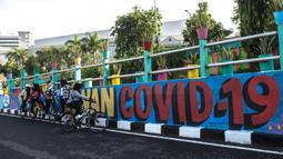 Pengendara sepeda beristirahat di dekat dinding bermural yang mengajak orang untuk memakai masker di tengah pandemi Covid-19 di Surabaya, Jawa Timur, Minggu (25/10/2020). Dinding itu dipenuhi dengan pesan untuk mematuhi protokol kesehatan di tengah pandemi Covid-19. (Juni Kriswanto/AFP)