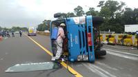 Kendaraan yang tengah mengangkut penumpang pasien positif Covid-19 terguling di Tol Jagorawi,Rabu (13/1/2021). (Liputan6.com/Achmad Sudarno)