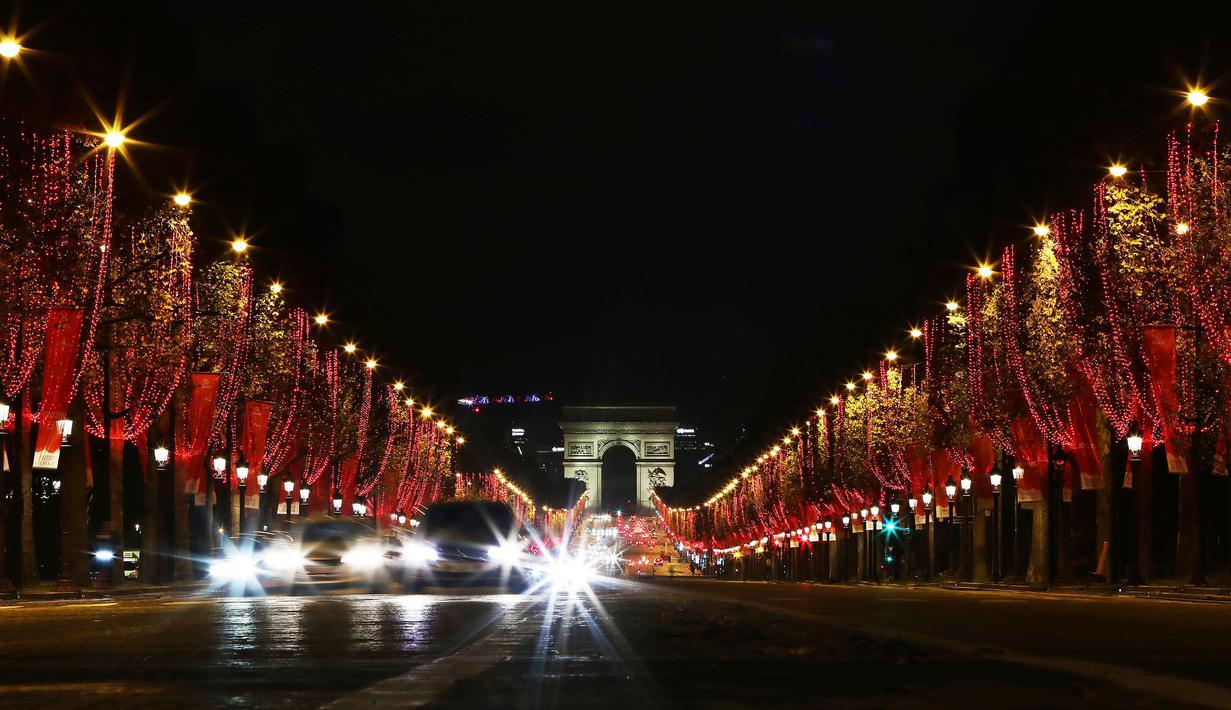Champs-Elysees Avenue dan Arc de Triomphe tampak terang usai lampu Natal dinyalakan di Paris, Prancis, pada 22 November 2020. Upacara penyalaan lampu digelar pada Minggu (22/11), tetapi penonton tidak diizinkan datang ke lokasi lantaran diberlakukannya kebijakan lockdown COVID-19. (Xinhua/Gao Jing)