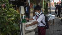 Seorang siswa mencuci tangan sebelum memasuki sekolah sebelum mengikuti pembelajaran tatap muka (PTM) di sebuah sekolah di Surabaya, Jawa Timur, Senin (6/9/2021). Pemerintah kembali membuka sekolah di tengah pandemi COVID-19. (JUNI KRISWANTO/AFP)