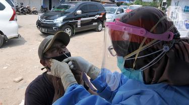 Paramedis melakukan swab antigen kepada pemudik di perbatasan Depok-Bogor, Jalan Raya Parung-Ciputat, Depok, Jawa Barat, Minggu (16/5/2021). Mulai hari ini, diberlakukan swab antigen kepada para pemudik yang akan kembali ke wilayah Depok. (merdeka.com/Arie Basuki)