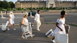 """Sejumlah orang berpakaian putih membawa peralatan dan kursi untuk mengikuti makan malam bersama atau """"Diner en Blanc"""" yang ke-30 di Paris, Prancis (3/6). (AFP/Francois Guillot)"""