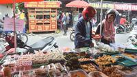 """Pembeli memilih takjil untuk berbuka puasa di """"Kampoeng Ramadhan Jogokariyan"""" di Jalan Jogokaryan Yogyakarta, Senin (21/5). Kampoeng Ramadhan Jogokaryan adalah salah satu program dari masjid Jogokariyan untuk menyemarakan Ramadan. (Liputan6.com/Gholib)"""