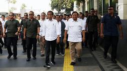 Presiden terpilih Joko Widodo atau Jokowi (kiri) bersama Ketua Umum Partai Gerindra Prabowo Subianto berjalan usai keluar dari Stasiun MRT Senayan, Jakarta, Sabtu (13/7/2019). Jokowi dan Prabowo mendapat pengawalan ketat Paspampres saat menuju FX Sudirman untuk makan siang. (Liputan6.com/JohanTallo)