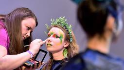 """Seorang makeup artist merias model saat mengikuti kompetisi makeup di International """"Crystal Angel"""" Festival of Hairdressing ke-15 di Kiev (22/4). (AFP/Sergei Supinsky)"""