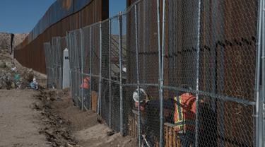 Pekerja menyelesaikan pembangunan tembok yang memisahkan AS dengan Meksiko, Rabu (25/1). Rencananya Trump Wall atau Tembok Trump akan dibangun di perbatasan AS dan Meksiko sepanjang 3.200 kilometer. (AP PHOTO)