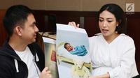 Ayu Dewi dan suami memperlihatkan foto anak kedua mereka saat jumpa pers di Rumah Sakit kawasan Pondok Indah, Jakarta, Senin (10/7). Ayu Dewi berharap anaknya nanti memiliki akhlak yang indah seperti Nabi Muhammad SAW. (Liputan6.com/Herman Zakharia)