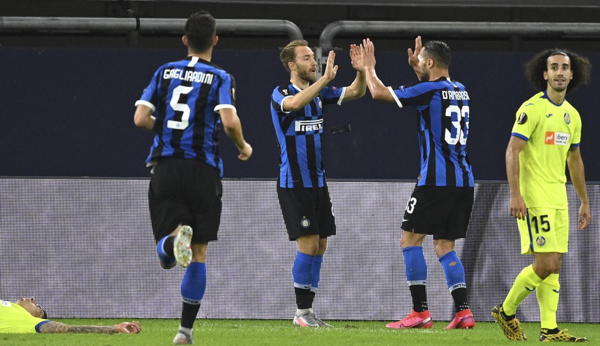Gelandang Inter Milan,  Christian Eriksen (tengah) berselebrasi usai mencetak gol ke gawang Getafe pada pertandingan babak 16 besar Liga Europa di Veltins-Arena di Gelsenkirchen, Jerman, Rabu, (5/8/2020). Inter menang 2-0 atas Getafe dan melaju ke perempat final.  (AP Photo/Ina Fassbender)