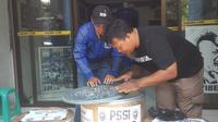 Pengurus Viking Persib Club (VPC), Yana Umar (kanan) menghitung uang hasil penggalangan dana untuk sanksi Persib Bandung. (Liputan6.com./Kukuh Saokani).