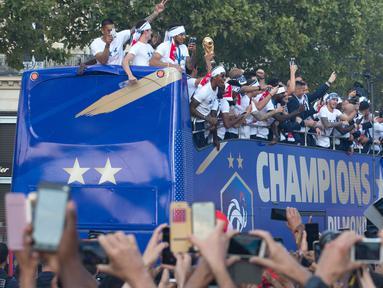 """Timnas Prancis mengikuti pawai dengan bus atap terbuka merayakan juara Piala Dunia 2018 di sepanjang Champs Elysees, Paris, Senin (16/7). Prancis menggelar pesta besar penyambutan sekaligus parade kemenangan bagi skuad """"Les Bleus"""". (AP/Claude Paris)"""
