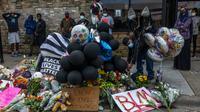 Bunga dan balon memenuhi lokasi kematian George Floyd oleh polisi di Minneapolis, Minnesota, Amerika Serikat, Rabu (27/5/2020). Unjuk rasa damai berubah menjadi kerusuhan setelah polisi menembaki mereka dengan gas air mata dan peluru busa. (Kerem Yucel/AFP)