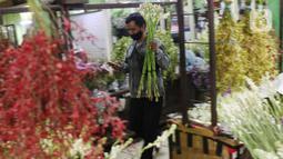 Warga membeli bunga potong untuk hiasan Lebaran di Rawa Belong, Jakarta Barat, Rabu (12/6/2021). Menyambut Hari Raya Idul Fitri 1442 H, banyak warga memburu bunga potong untuk menghias rumah. (Liputan6.com/Angga Yuniar)