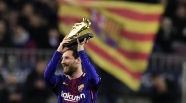 Bintang Barcelona, Lionel Messi mengangkat sepatu emas yang diterima setelah berhasil menjadi pencetak gol terbanyak Eropa pada 2017 di Camp Nou stadium, Barcelona, (17/12/2017). (AFP/Javier Soriano)
