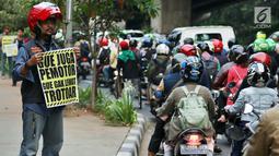 Aktivis Koalisi Pejalan Kaki membawa poster saat aksi peduli pejalan kaki di kawasan pedestrian Kasablanka, Jakarta, Kamis (22/8). Mereka menyerukan agar tidak menggunakan trotoar sebagai tempat parkir dan berjualan.(Liputan6.com/JohanTallo)