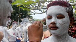 "Para pemuda melukis diri mereka untuk persiapan ritual Hindu yang disebut ""Grebeg"" di Desa Tegallalang, Bali, Rabu (30/1). Tradisi ritual berkeliling kampung dengan riasan tubuh warna-warni itu dipercaya sebagai penangkal Roh jahat. (AP/Firdia Lisnawati)"