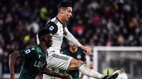 Striker Juventus, Cristiano Ronaldo, berebut bola dengan bek Bologna, Ibrahima Mbaye, pada laga Serie A Italia di Stadion Juventus, Turin, Sabtu (19/10). Juventus menang 2-1 atas Bologna. (AFP/Marco Bertorello)