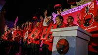 Aksi Ketum PDIP, Megawati Soekarnoputri dan para kader mengangkat tangan dengan posisi jari mengacungkan simbol metal pada pesta rakyat di Jakarta, Minggu (18/2). PDIP mendapatkan nomor urut tiga sebagai peserta Pemilu 2019. (Liputan6.com/Faizal Fanani)