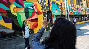 Warga foto di dekat karya seni Mural di Taman Ismail Marzuki (TIM), Cikini, Jakarta, Selasa (11/9). Mural tersebut dibuat oleh seniman asal Kolombia Diana Ordonez. (Liputan6.com/Faizal Fanani)
