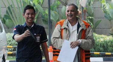 Direktur Utama nonaktif PLN Sofyan Basir (kanan) tiba di Gedung KPK, Jakarta, Kamis (27/6/2019). Sofyan berjalan menuju lobi KPK dengan memakai rompi tahanan dan tangan terborgol, tetapi dia terlihat menutupinya dengan lembaran kertas. (merdeka.com/Dwi Narwoko)