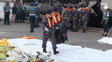 Personil TNI AL membawa kantong jenasah yang diturunkan dari KRI Torani di Pelabuhan JICT 2, Jakarta, Kamis (1/11). 189 orang menjadi korban jatuhnya pesawat Lion Air JT-610, Senin (29/10) lalu. (Liputan6.com/Helmi Fithriansyah)