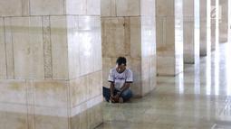 Seorang pria duduk di lorong Masjid Istiqlal, Jakarta, Kamis (17/5). Di Masjid Istiqlal ini ada sekitar 4000 kotak makanan yang dibagikan per harinya pada Ramadan tahun ini. (Liputan6.com/Immanuel Antonius)
