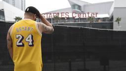 Gennesys Cabral, dari Los Angeles, mengenakan jersey Kobe Bryant di luar Staples Center, Los Angeles (26/1/2020). Selain Bryant, empat orang lainnya dalam helikopter itu juga dinyatakan meninggal dunia. (AP Photo/Chris Pizzello)