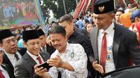 Mendikbud Nadiem Makarim berswafoto dengan sejumlah guru usai upacara peringatan Hari Guru 2019. (Ady anugrahadi/Liputan6.com)